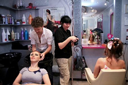 Barber washing hair with shampoo young woman in a beauty salon