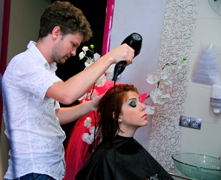 stylist drying woman hair in beauty salon.
