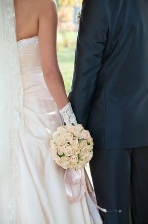 white wedding bouquet in the hands of the bride and groom