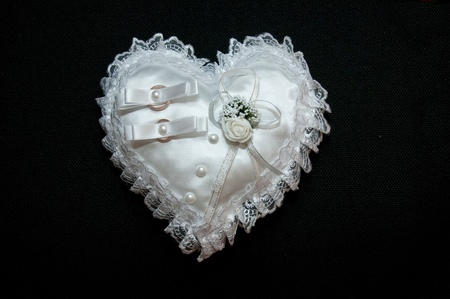 Two wedding rings in a heart-shaped pillow