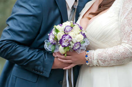 blue and white wedding bouquet in the hands of the bride and groom