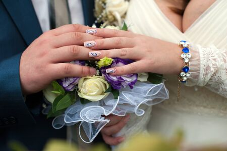 blue and white wedding bouquet in the hands of the bride and groom Stock Photo
