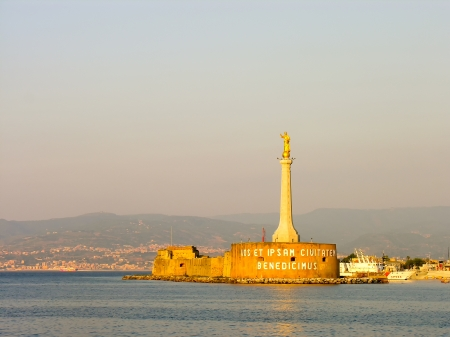 Italy, Sicily, Messina, sunrise view of the city and the Madonna statue at the port entrance