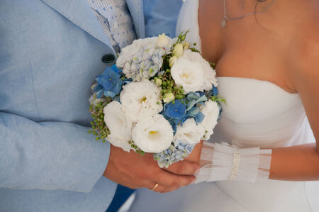 Hands with wedding rings and beautiful blue and white fresh flowers wedding bouquet Stock Photo