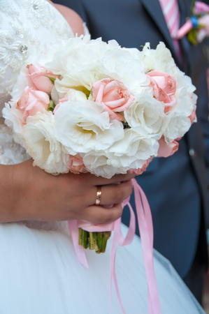 Hands with wedding rings and beautiful  fresh flowers wedding bouquet Stock Photo