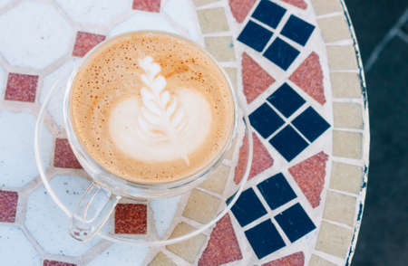 Cappuccino on mosaic table, in pastel colors. 스톡 콘텐츠