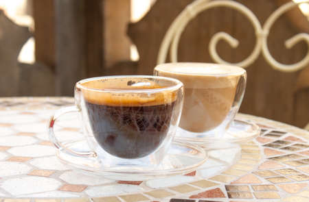 Americano and cappuccino, black coffee on mosaic table.