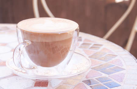 Cap of cappuccino in glass on mosaic table, in pastel colors. 스톡 콘텐츠