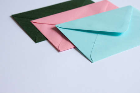 Colorful envelopes and white cardboard on table. Mockup. Office concept.