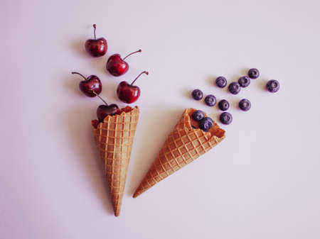 Ice cream waffle cones with blueberries and sweet cherries, pastel minimal flat lay top view. Stockfoto