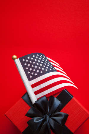 American flag and red gift box with blue ribbon on red background. Independence Day concept, 4th of July banner.