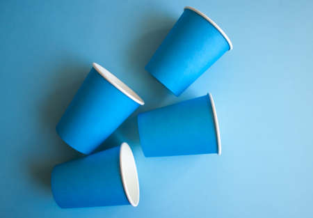 Blue paper cups on blue background. Set for party.