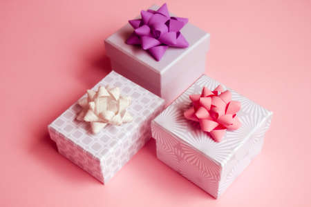 Three light gray gift boxes with colorful bows on pink background. Festive concept.