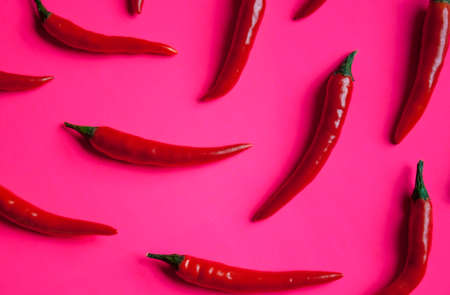 Fresh red cayenne peppers on neon pink vibrant background.