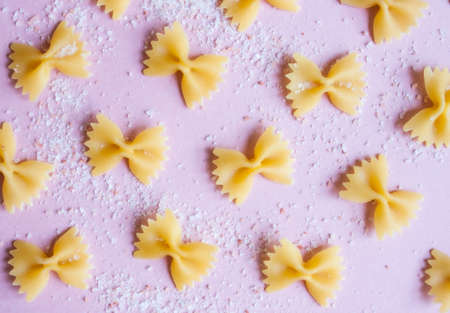 Italian pasta farfalle pattern viewed from above and pink Himalayan salt on lilac background. Food concept.