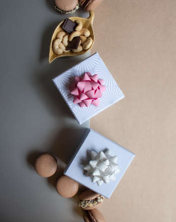 Two white gray gift boxes, chocolate macarons and bowl of cashew nuts on silver and kraft paper background. Stockfoto