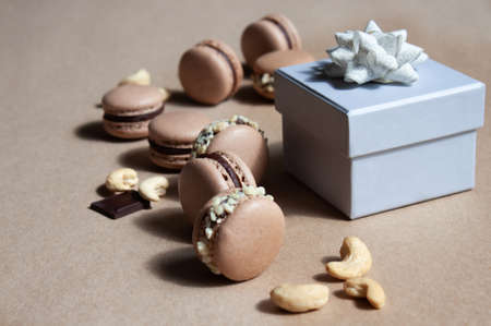 White gray gift boxe and dark chocolate macarons with cashew nuts on kraft paper background. Festive concept. Stockfoto