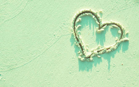Heart symbol on sand in mint green tone, love mood, vacation concept. Stockfoto