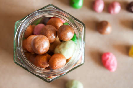 Glass jar full of colorful chocolate handmade gourmet dragee candies on Kraft paper background.