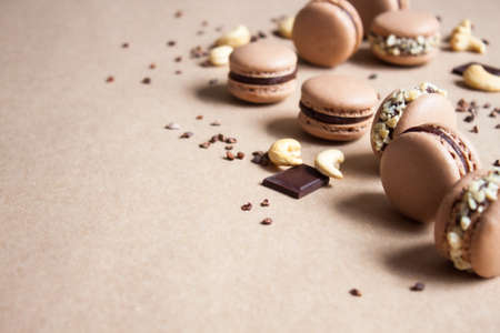 Dark chocolate macarons with cashew nuts and cocoa nibs on kraft paper background.