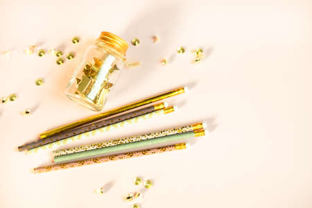 Golden paper clips and glass jar, cute pastel colors pencils on light beige background. Top view, flat lay. Minimal school or office stationery.
