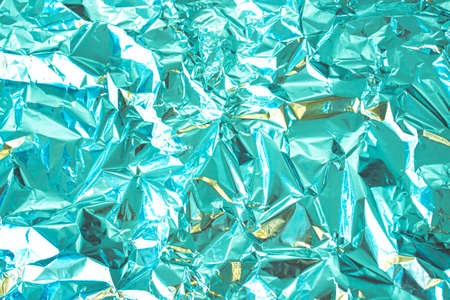 Abstract background made of textured mint azure toned aluminum foil. Backdrop for design.