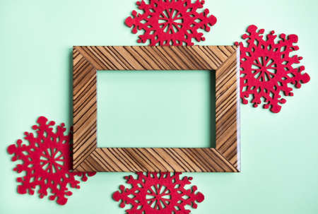 Brown shiny wooden frame and Christmas vibrant red snowflakes on mint green background. Festive concept. Perfect backdrop for holidays.