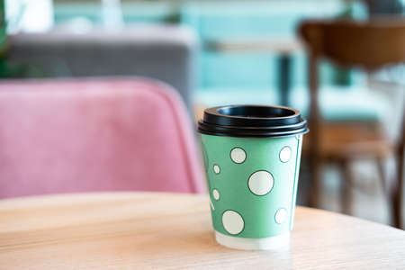Mint green disposable paper cup of coffee with black lid on light wooden table in shopping mall cafe. Lifestyle concept. 스톡 콘텐츠