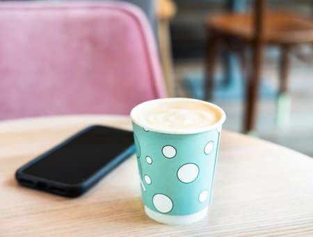 Mint green disposable paper cup of coffee and black cellphone on light wooden table in shopping mall cafe. Lifestyle concept.