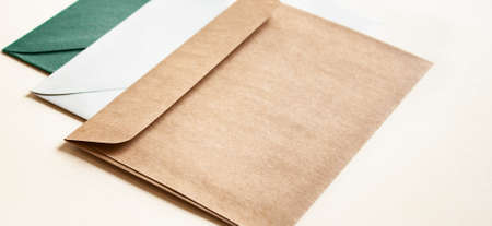 Natural colors envelopes on beige background. Office minimalistic concept.
