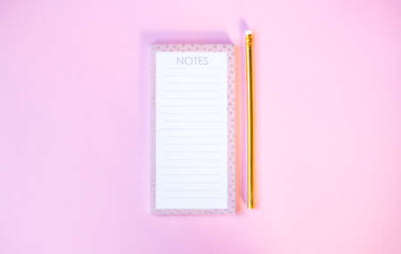Notebook and cute golden pencils on gradient pink background. Flat lay style.
