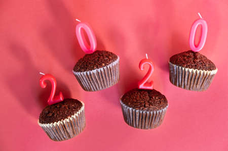 Classic dark chocolate cupcakes with red new year 2020 candles on Christmas happy red background.