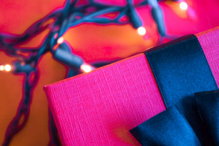 Pink yarrow box with navy blue ribbon on bright reddish background with Christmas lights. Futuristic concept.