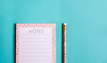 Pink notebook and cute golden pencils on trendy green background. Flat lay minimalism style.