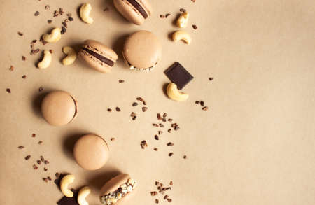 Dark chocolate macarons with cashew nuts and cocoa nibs on caramel color background.