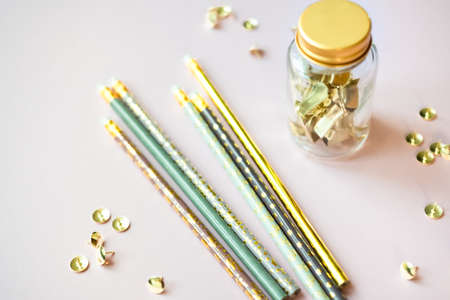 Golden paper clips and glass jar, cute pastel colors pencils on ashen beige gray background. Top view, flat lay. Minimal school or office stationery.
