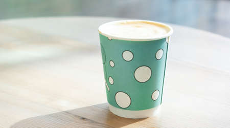 Mint green disposable paper cup of coffee on light wooden table in shopping mall cafe. Lifestyle concept.