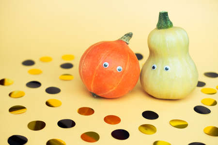 Two multicolored pumpkins and confetti on trendy orange background. Halloween funny holiday concept. 免版税图像