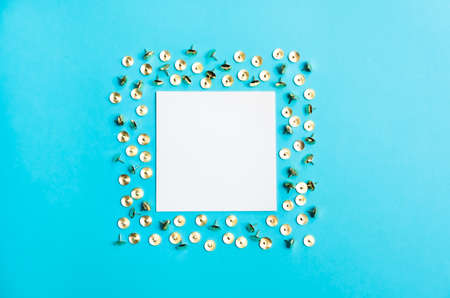 White square frame with golden shiny pushpins on trendy blue background. Flat lay minimalistic style. Trendy color. 版權商用圖片