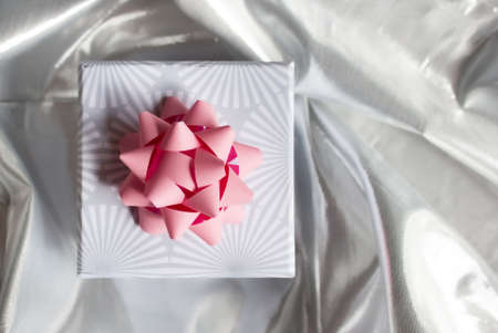 Gift box with pink bow on bright silver tissue background. Festive concept. Christmas mood.