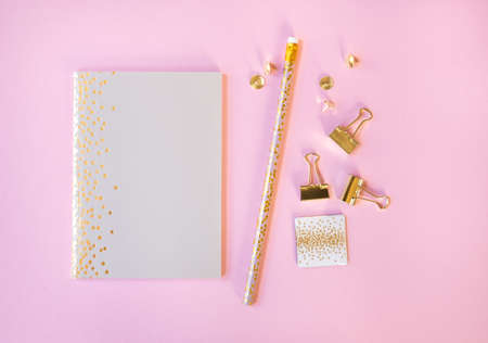 Beige notebook and pencil with golden polka dot print on light pink background. Flat lay style. 스톡 콘텐츠
