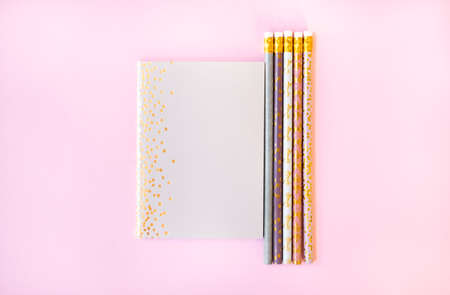Beige notebook and cute pencils with golden polka dot print on light pink background. Flat lay style. 스톡 콘텐츠