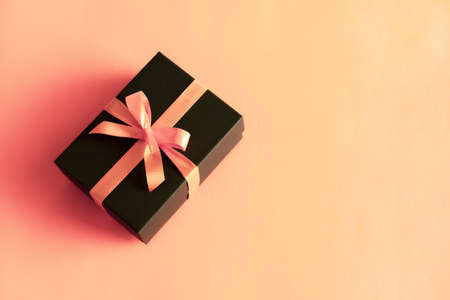 Black gift box with orange bow on pastel coral pink background. Flat lay festive minimal style. Stock Photo