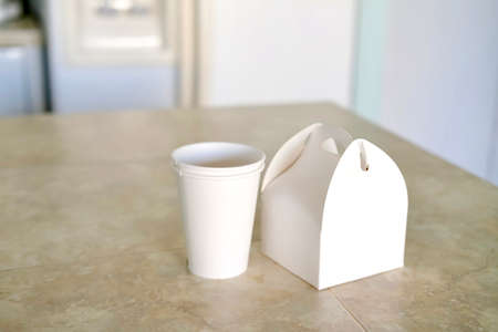 White paper cups and box on kitchen table. Food order to go concept.