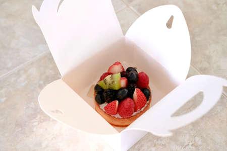 Fresh fruit tart in white paper box on table. Modern patisserie concept. Banco de Imagens