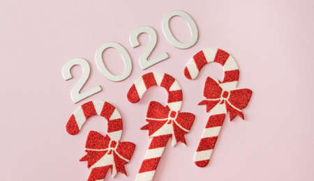 Silver Christmas decorations and red white candy canes on pastel pink background. Flat lay style. Holiday classic concept.
