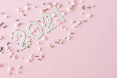 Silver Christmas decorations and sugar sprinkles on pastel pink background. Flat lay style. Holiday classic concept.