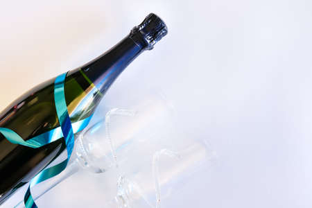 Dark blue bottle of champagne with shiny ribbon and two glasses on white background. Festive concept. Flat lay style.