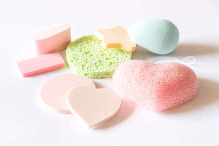 Assorted colorful pastel cosmetic sponges on white background. Beauty products concept. Flat lay, top view, copy space design.