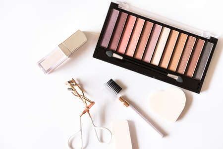 Assorted pastel colored cosmetic products, eye shadows palette, lip gloss, blow comb, eyelash curler, brush and sponges on white background. Beauty concept. Flat lay design.